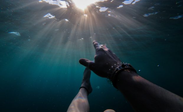 person underwater reaching up to light