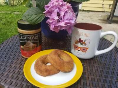 apple cider donut on a plate with coffee
